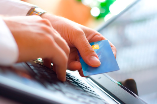 Image of hands holding a credit card and getting ready to make a payment on a computer.