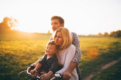 Family on a bike together near a field at sunset  family